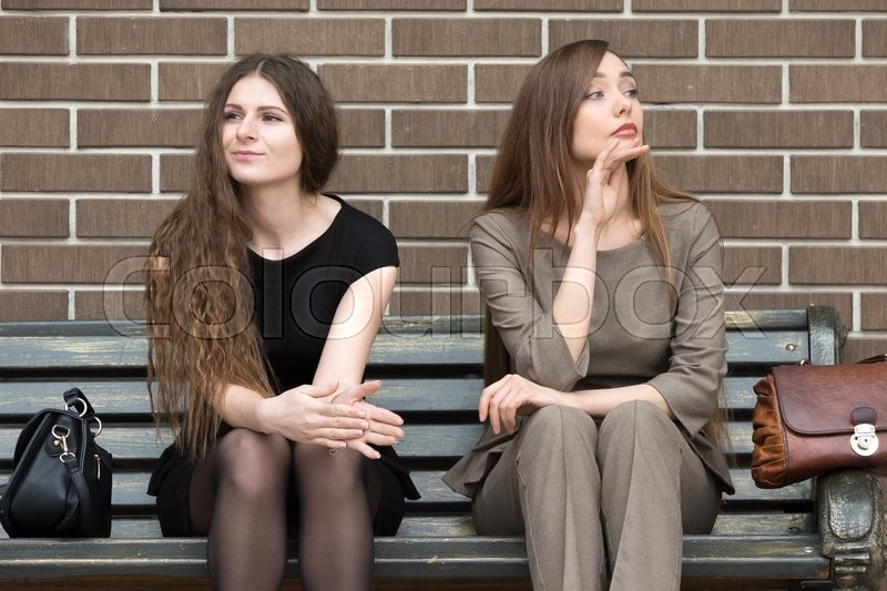 Stock image of 'Full length portrait of two beautiful young female rivals sitting side by side on bench. Attractive caucasian office women holding grudge against each other'