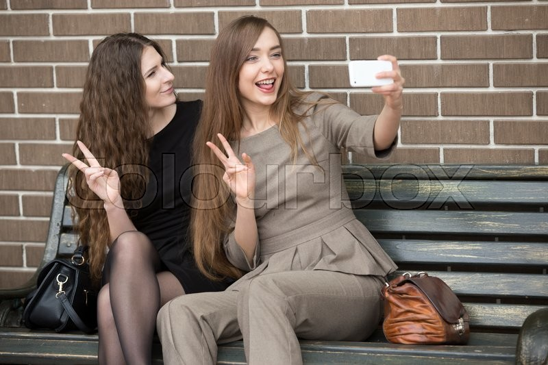 Stock image of 'Portrait of two beautiful young girlfriends sitting on bench and taking a selfie on the street. 2 Happy attractive women friends making self-portrait with smartphone'
