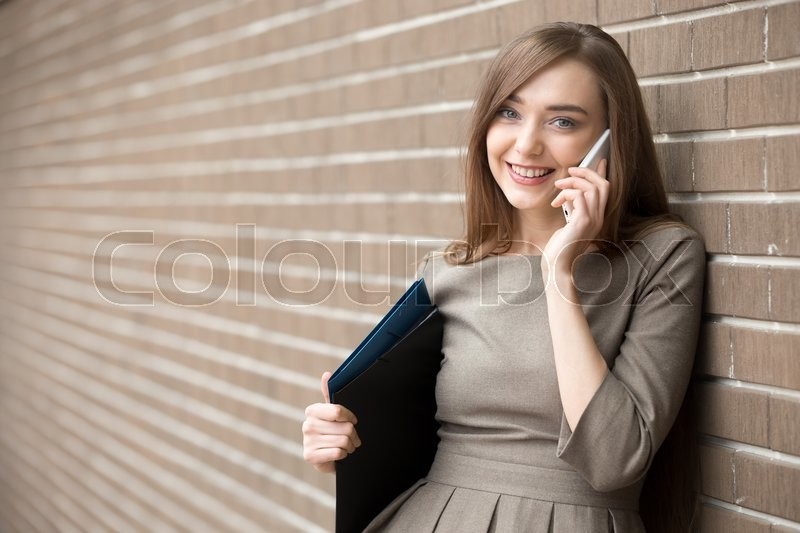 Stock image of 'Waist portrait of cheerful young woman standing in the street beside brick wall, talking on smartphone. Happy beautiful caucasian woman using mobile phone, making call, looking at screen. Copy space'