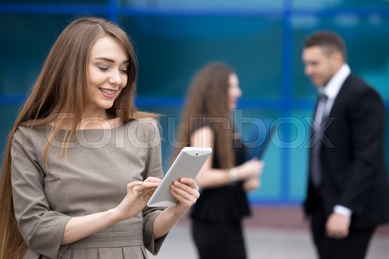 Stock image of 'Portrait of confident young woman looking at tablet screen with happy facial expression outdoors. Successful beautiful caucasian woman using app on the street with businesspeople on the background'