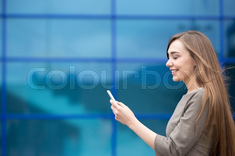 Stock image of 'Portrait of cheerful young woman sending message on smartphone outdoors. Happy beautiful caucasian woman using mobile phone, making call, looking at screen on the street in summer. Copy space'