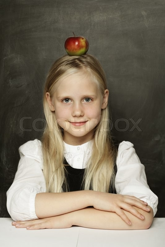 Stock image of 'Smiling schoolgirl sitting in classroom'