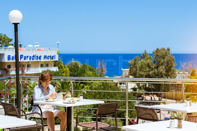 Editorial image of 'BALI, GREECE - APRIL 28, 2016: Elderly woman in blue shirt is having lunch on veranda of restaurant, overlooking the Cretan sea. Resort hotel Atali Village 4 star, Bali, Rethymno, Crete, Greece'