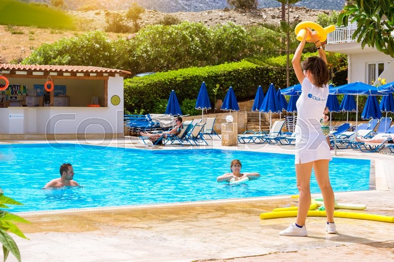 Editorial image of 'BALI, GREECE - APRIL 29, 2016: Animation at Resort hotel Atali Village 4 star. Cute girl in white beach suit conducts classes for tourists in water aerobics in pool with clean blue water. Bali, Rethymno, Crete, Greece'