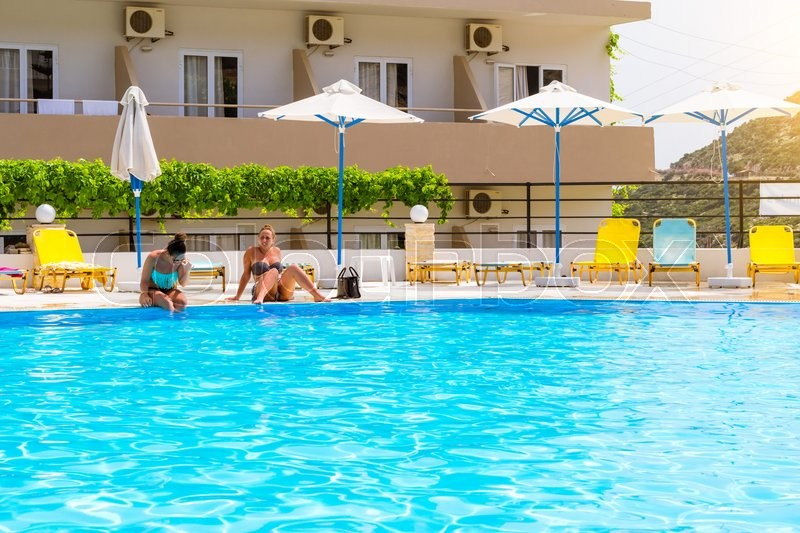 Editorial image of 'BALI, GREECE - APRIL 29, 2016: Relax and sunbathe by pool with clear blue water in Resort hotel Atali Village, 4 star. Beautiful girl in bikini sitting on edge of pool in middle of day. Bali, Rethymno, Crete, Greece'
