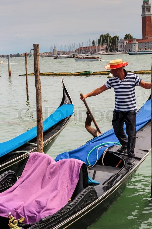 Stock image of 'VENICE, ITALY - 26 JUNE, 2014: Gondolier rides gondola. The profession of gondolier is controlled by a guild, which issues a limited number of licenses'