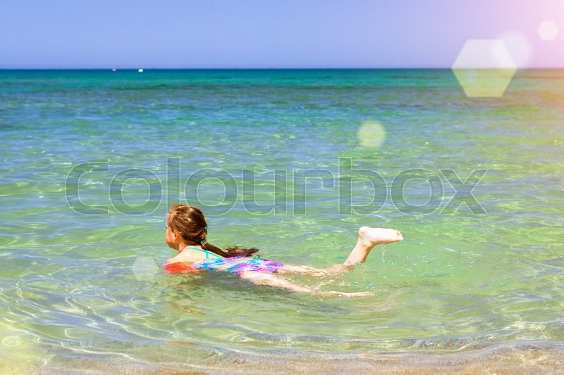 Stock image of 'BALI, GREECE - APRIL 28, 2016: Cute happy girl child relaxing and bathed on the shores of Cretan sea in rescue arm cover. Sunny sandy Livadi beach in sea Bay of resort village Bali, Rethymno, Crete, Greece'