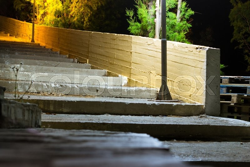 Stock image of 'BALI, GREECE - APRIL 29, 2016: Old street concrete stairs, illuminated by road lights. Dark quiet lonely night in resort mediterranean village. Bali, Rethymno, Crete, Greece'