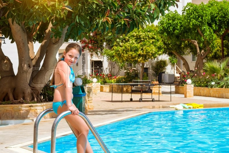 Stock image of 'BALI, GREECE - APRIL 29, 2016: Cute little teenage girl in swimsuit standing at entrance to pool in middle of day. Relax and sunbathe by pool with clear blue water in Resort hotel Atali Village, 4 star. Bali, Rethymno, Crete, Greece'