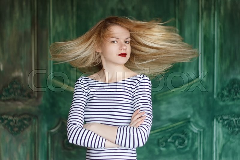 Stock image of 'Blonde with red lips in a striped shirt on a green background a grunge wall'