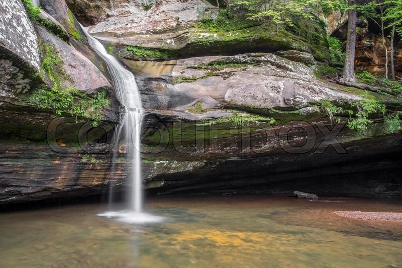 Stock image of 'Cedar Falls, a beautiful waterfall in the Hocking Hills of Ohio, cascades down a sandstone cliff before finally plunging into a pool below.'