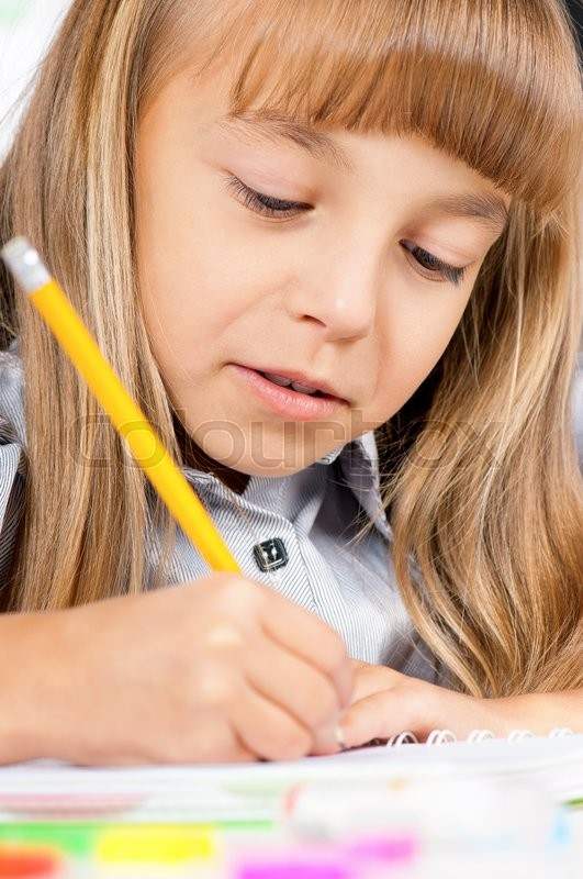 Stock image of 'Portrait of a adorable little girl in school at the desk'