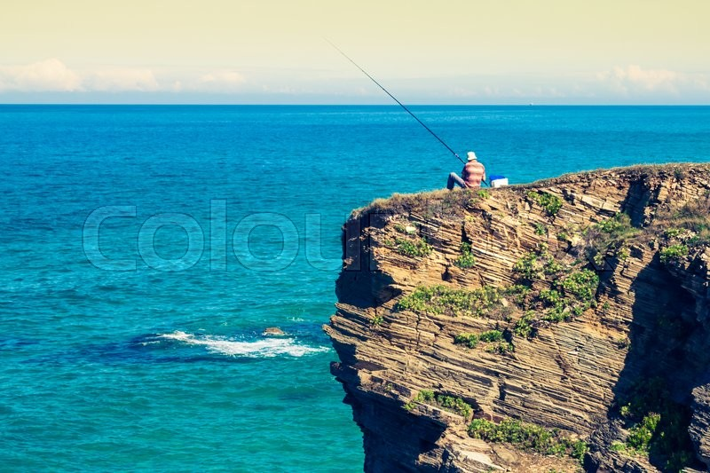 Stock image of 'Fisherman on the rocks,Ribadeo, Spain'