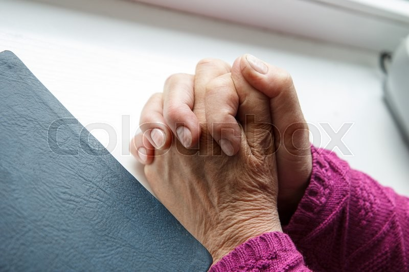 Stock image of 'An old person praying to God with the Bible beside her'
