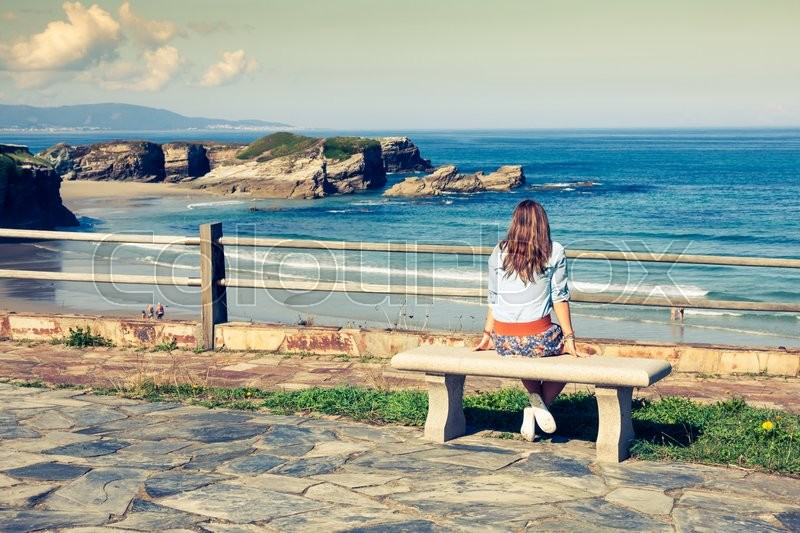 Stock image of 'Young woman sitting on bench facing the sea'