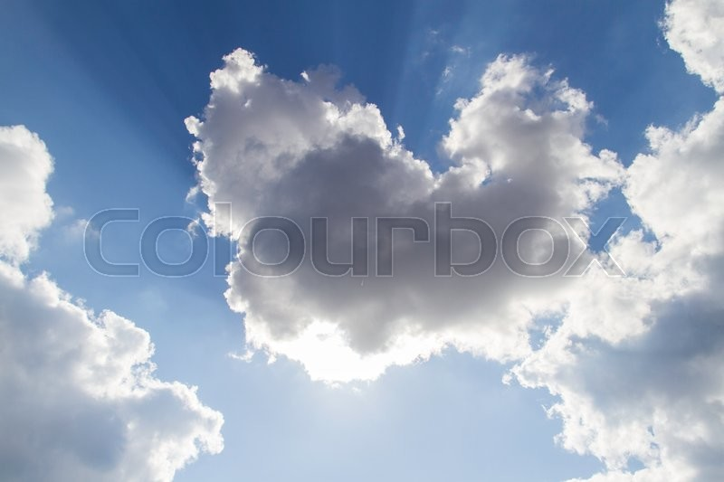 Stock image of 'sun shinning from behind clouds in a blue sky'