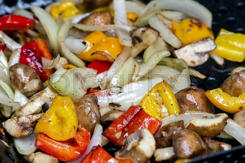 Stock image of 'peppers , mushrooms and onions grilling on a bbq'