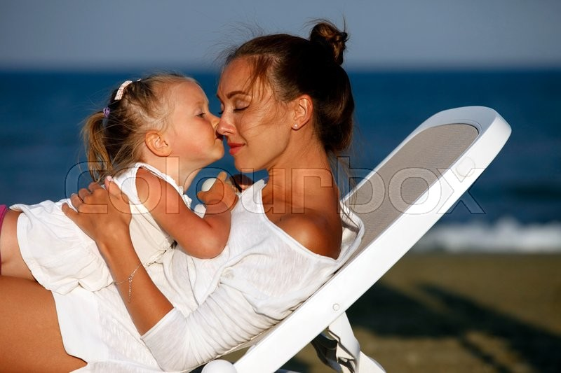 Stock image of 'Happy mother holding her daughter on the beach'