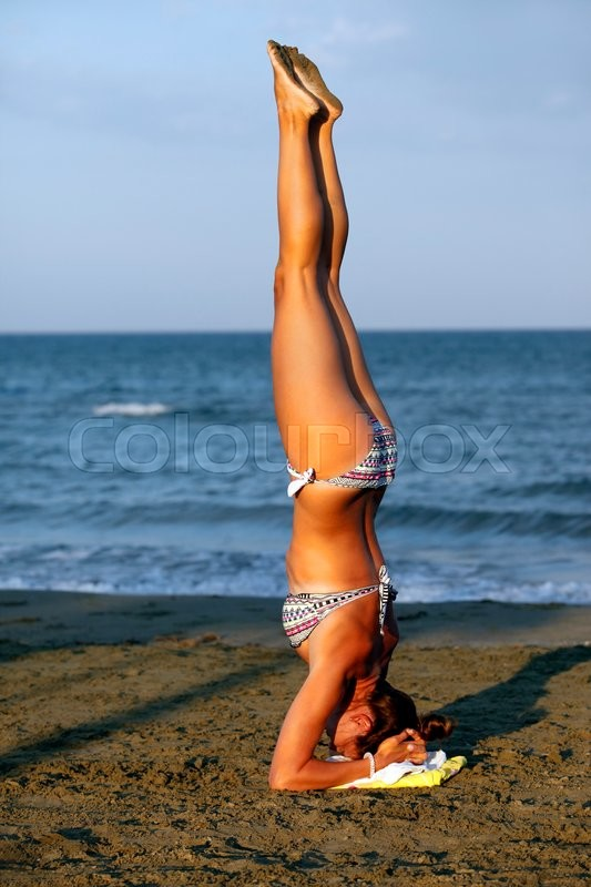 Stock image of 'Young woman practicing yoga on the sea beach at sunset'