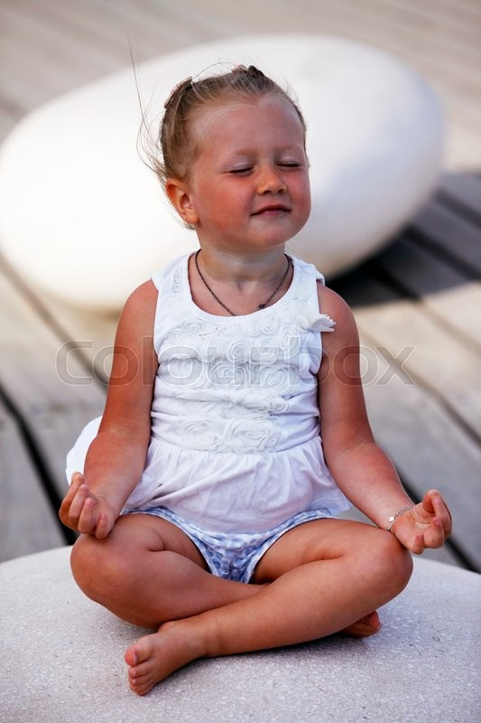 Stock image of 'Adorable little girl doing yoga sitting on the big stone'