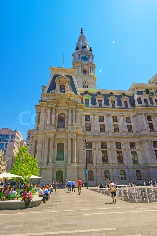 Editorial image of 'Philadelphia, USA - May 4, 2015: Philadelphia City Hall with fountain on Penn Square. Tourists on the square. Pennsylvania, USA. With special sun flare'