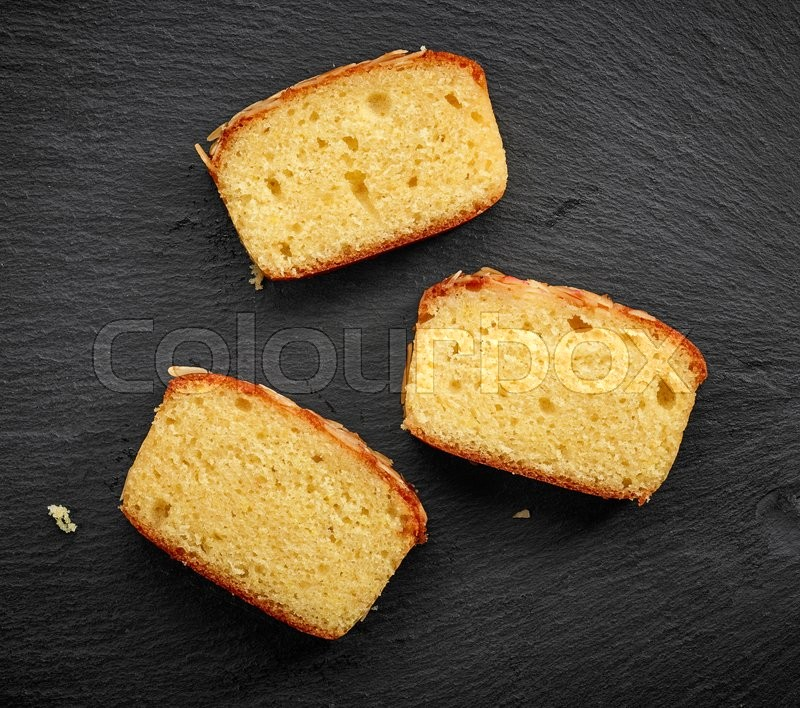 Stock image of 'freshly baked biscuit cake slices on black stone background, top view'