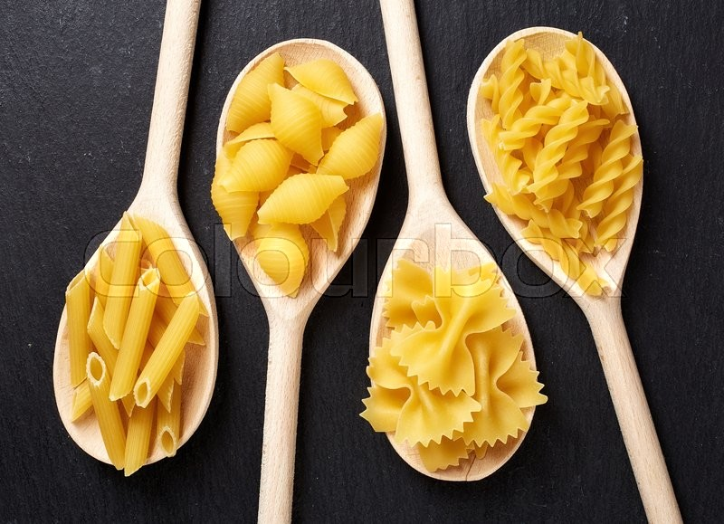 Stock image of 'Various types of pasta in wooden spoons on black stone table, top view'