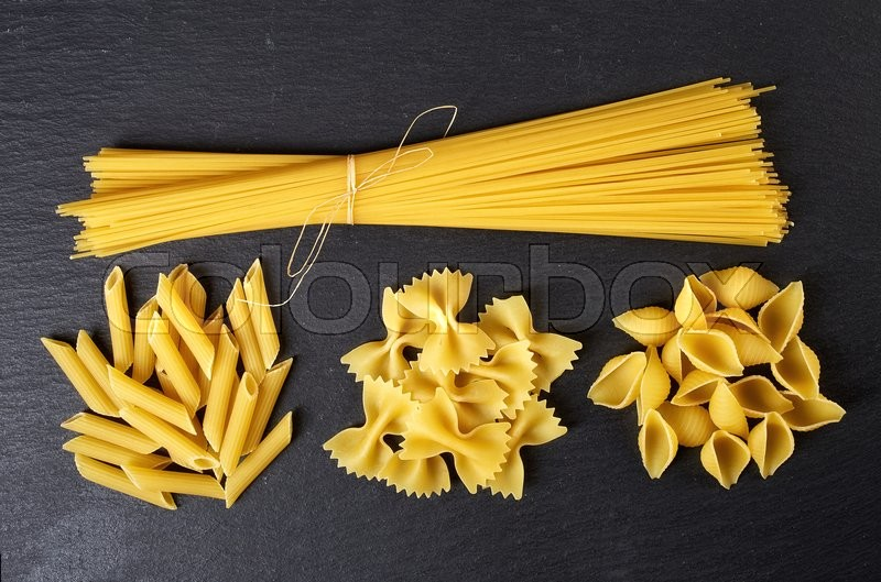 Stock image of 'Various types of pasta on black background, from above'