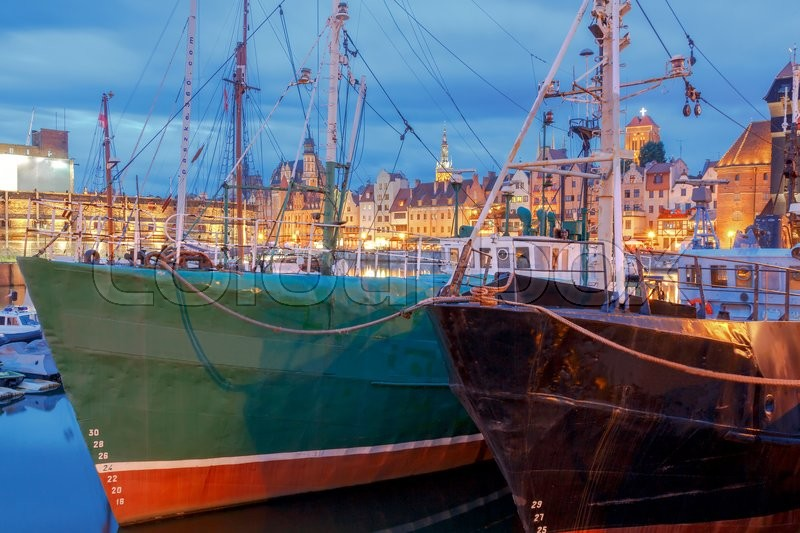 Stock image of 'Multi-colored facades and boat on the central waterfront in Gdansk at night.'