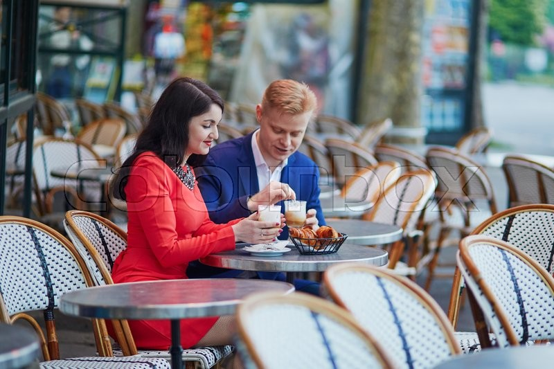 Stock image of 'Happy couple drinking coffee in an outdoor cafe in Paris. Tourists enjoying their vacation in France. Romantic date or traveling couple concept'