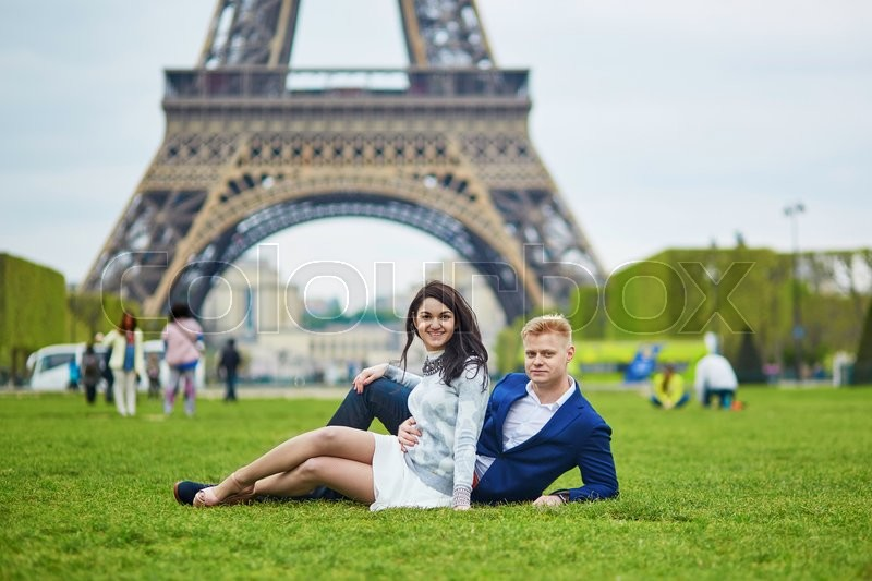 Stock image of 'Happy couple lying on the grass near the Eiffel tower. Tourists enjoying their vacation in France. Romantic date or traveling couple concept'