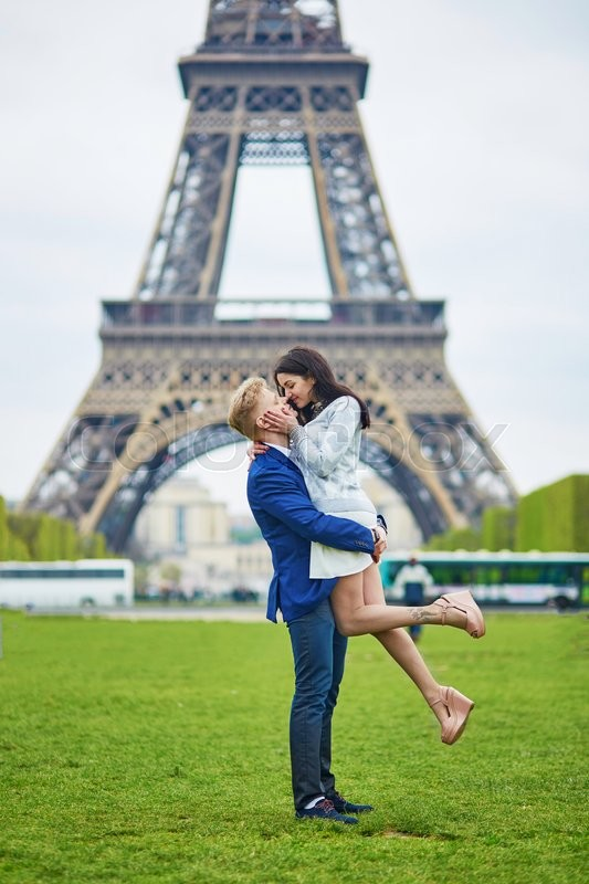 Stock image of 'Happy couple near the Eiffel tower. Tourists enjoying their vacation in France. Romantic date or traveling couple concept'