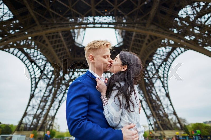 Stock image of 'Happy couple kissing under the Eiffel tower. Tourists enjoying their vacation in France. Romantic date or traveling couple concept'