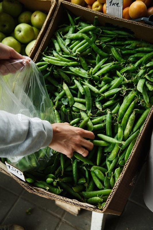 Stock image of 'woman with your hands puts the pods of young peas in a plastic bag from a large box on the market'