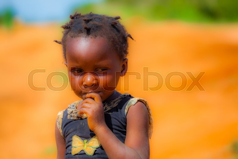Stock image of 'A very small young girl in the middle of african savana'