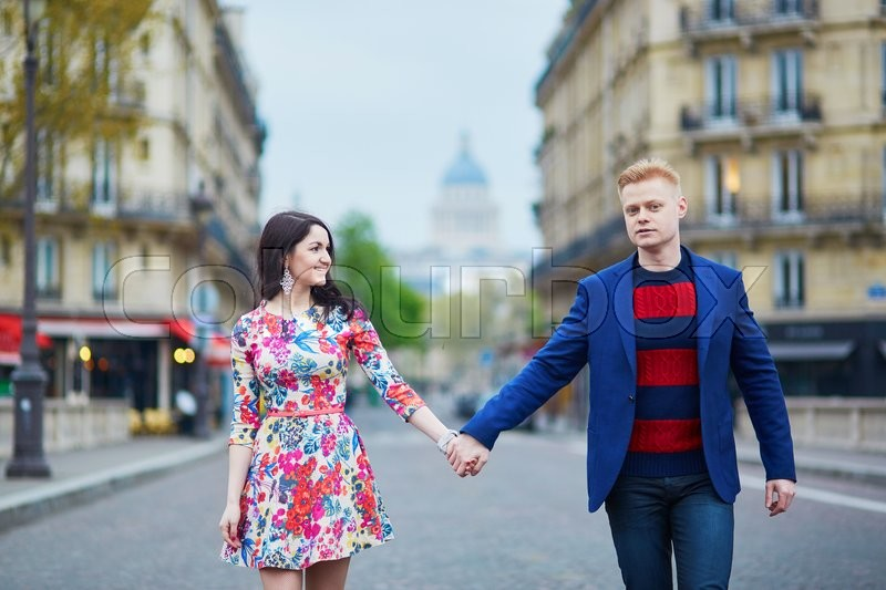 Stock image of 'Happy couple walking in Paris. Tourists enjoying their vacation in France. Romantic date or traveling couple concept'