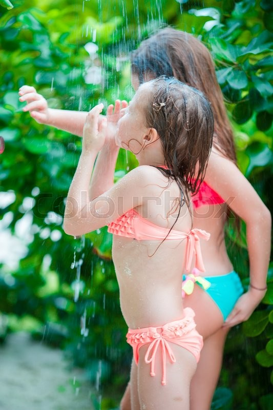 Stock image of 'Adorable little girls under beach shower on tropical beach'