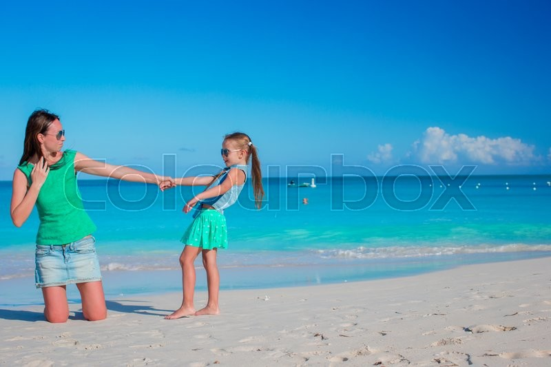 Stock image of 'Beautiful mother and her adorable little daughter at beach'