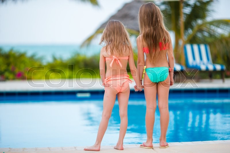 Stock image of 'Adorable little girls playing in outdoor swimming pool'