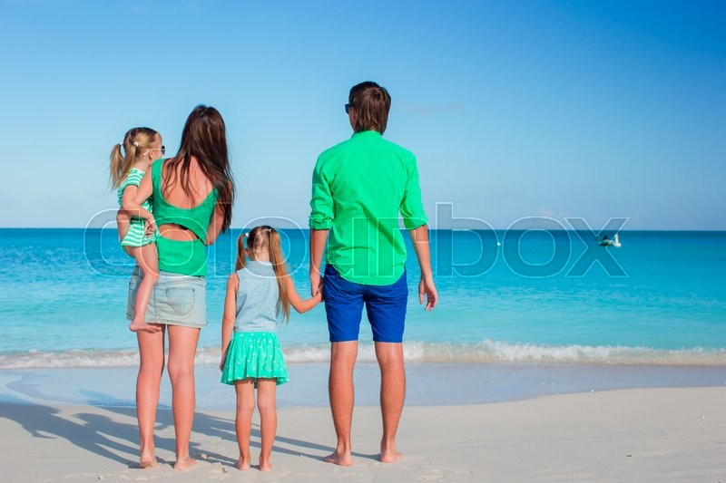 Stock image of 'Happy beautiful family on white beach having fun'