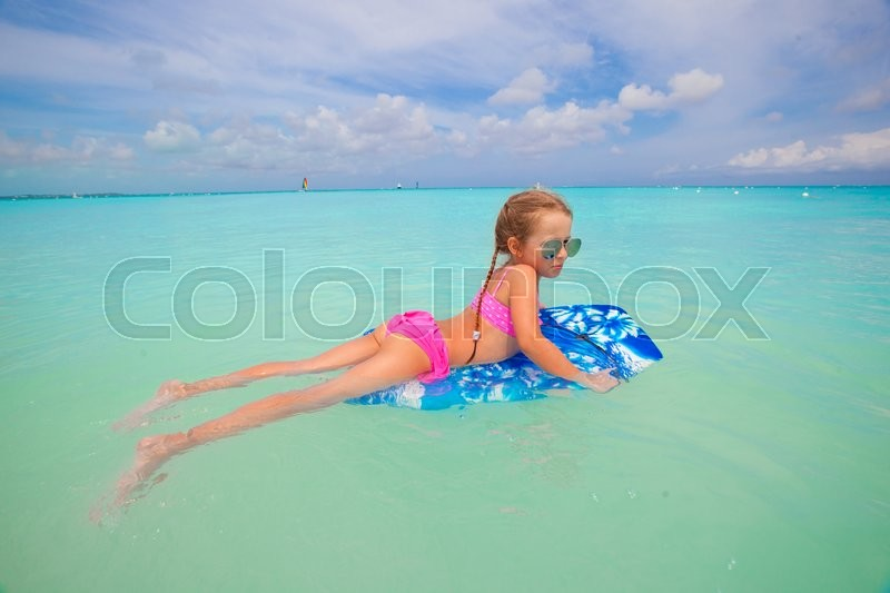 Stock image of 'Little cute girl surfing in the turquoise sea'