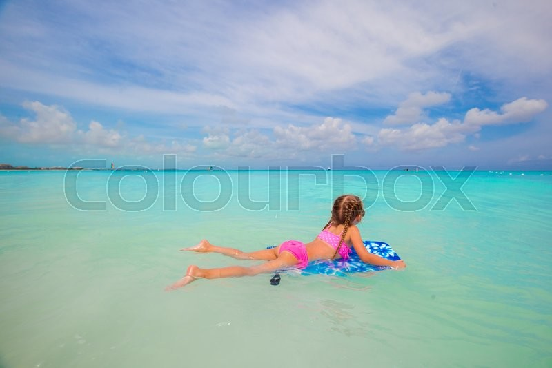 Stock image of 'Little adorable girl on a surfboard in the turquoise sea'