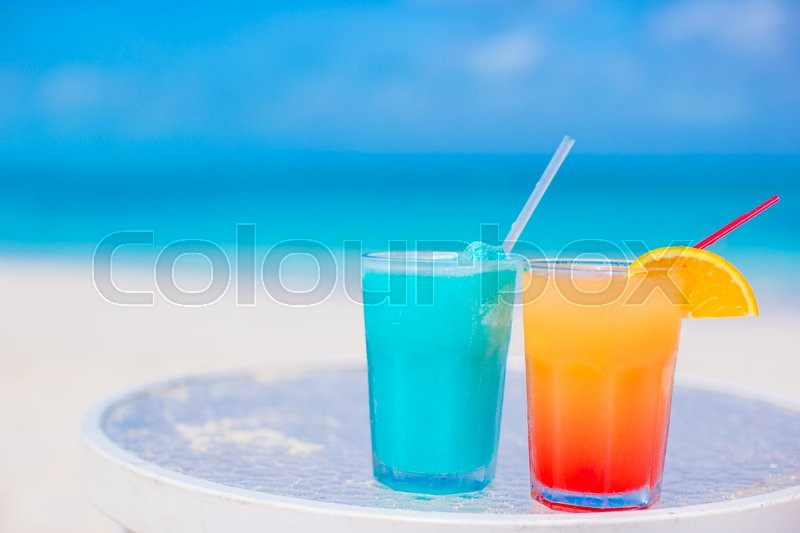 Stock image of 'Two tasty alcoholic cocktails on tropical white beach'