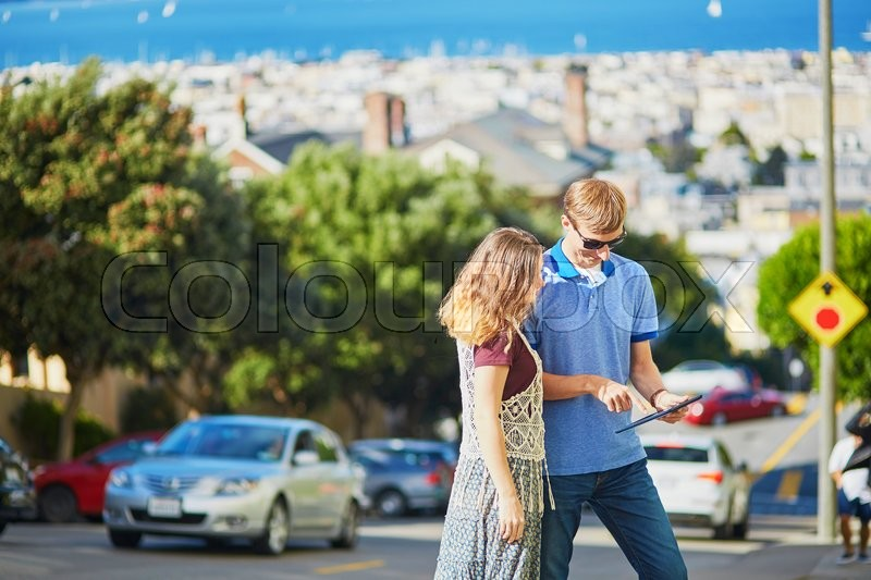 Stock image of 'Romantic couple of tourists using tablet and planning their itinerary in San Francisco, California, USA'