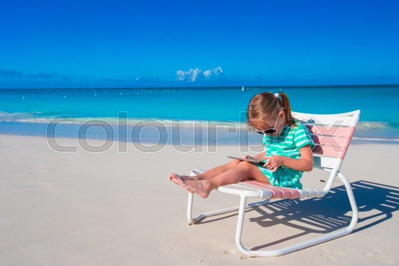 Stock image of 'Little girl with laptop on beach during summer vacation'