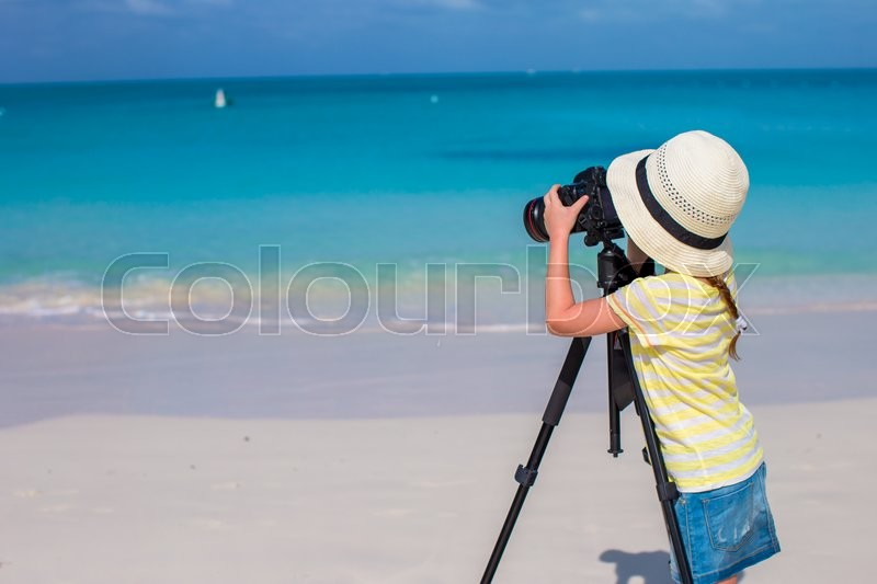 Stock image of 'Little cute girl taking pictures on phone at tropical beach'