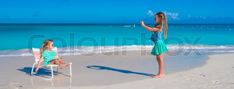 Stock image of 'Little girls having fun at tropical beach playing together outdoors'