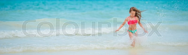 Stock image of 'Adorable little girl have fun at shallow water during summer vacation'
