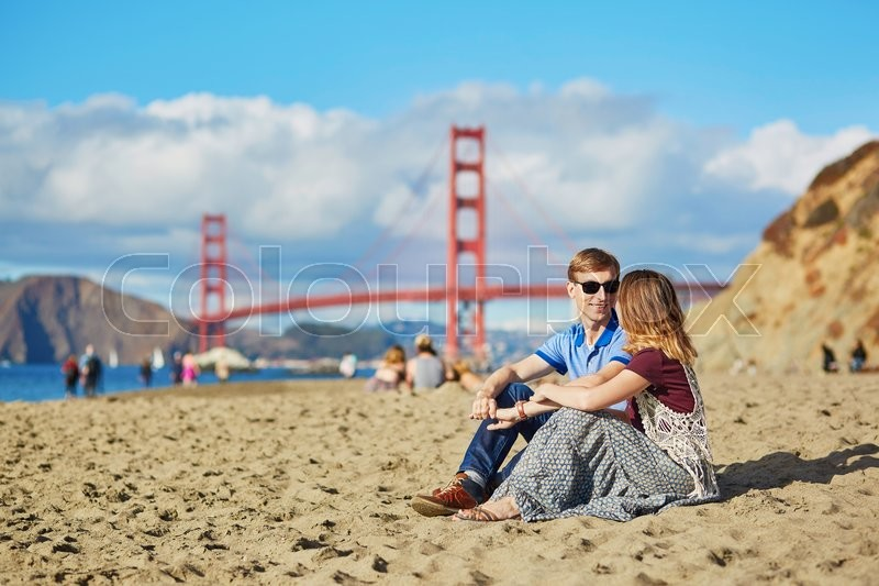 Stock image of 'Romantic loving couple having a date on Baker beach in San Francisco, California, USA. Golden gate bridge in the background'