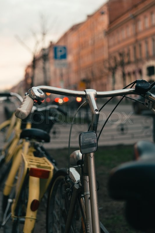 Stock image of 'the bike is strapped to the fence on a city street on a spring day'